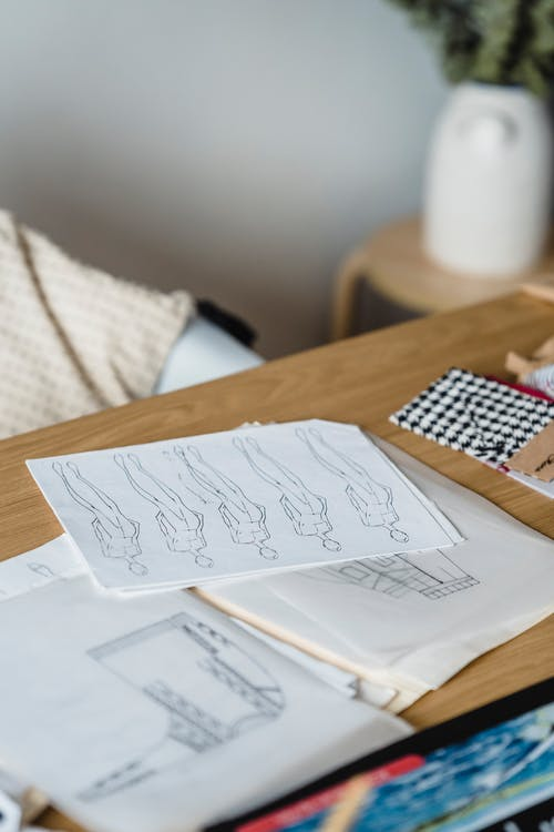 Papers with creative drafts placed on wooden table with sewing patterns and samples of textile in light room of atelier