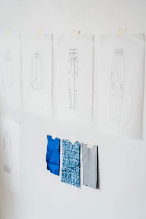 Papers with sketches of stylish garments attached on white wall with tape near samples of colorful fabric in light modern atelier