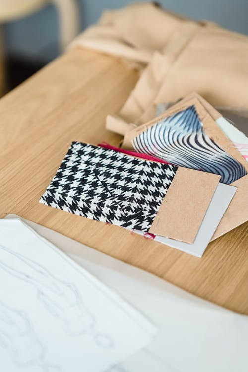 From above samples of colorful fabric placed on wooden table with brown cloth and sketches on paper in light modern atelier
