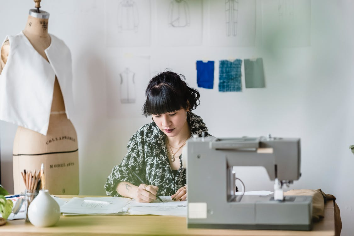 Asian woman drawing sketches at table with sewing machine