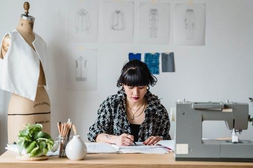 Concentrated ethnic woman drawing sketch while sitting at table near sewing machine and dummy