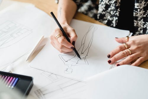 Crop unrecognizable female designer in golden rings drawing human figure with pencil on paper sheet at desk