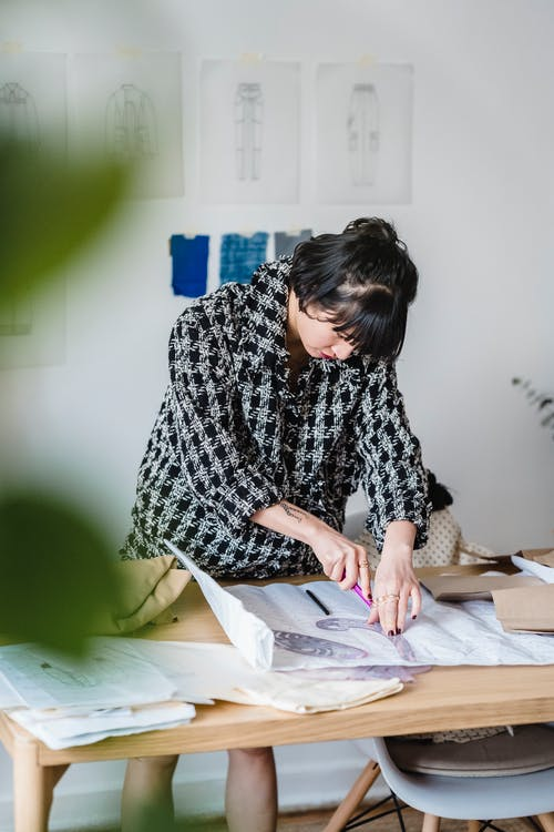 Attentive Asian dressmaker tracing on paper with sewing ruler