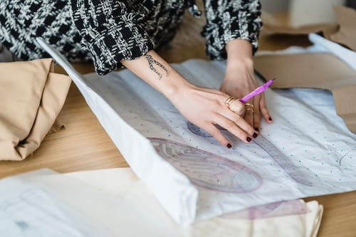 Crop unrecognizable tattooed female tailor measuring paper with curved ruler against fabric on table in atelier