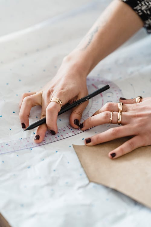 From above of crop anonymous seamstress with pencil measuring paper and cardboard template with curved ruler in workroom