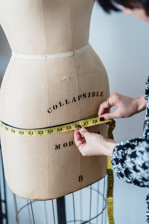 Crop unrecognizable female dressmaker with flexible ruler measuring hip line of dummy while working in studio