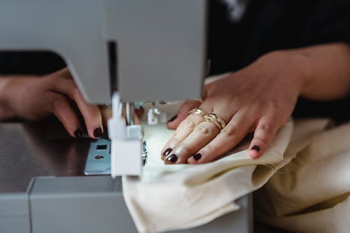 Crop anonymous talented female dressmaker with manicure and rings sewing white fabric on sewing machine while working in modern light workshop