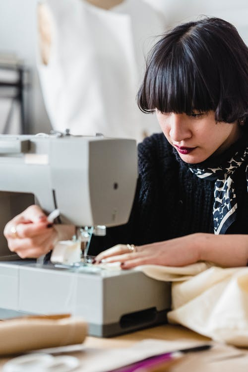 Concentrated Asian female tailor with black short hair sewing textile on machine while working in light modern workshop with mannequin