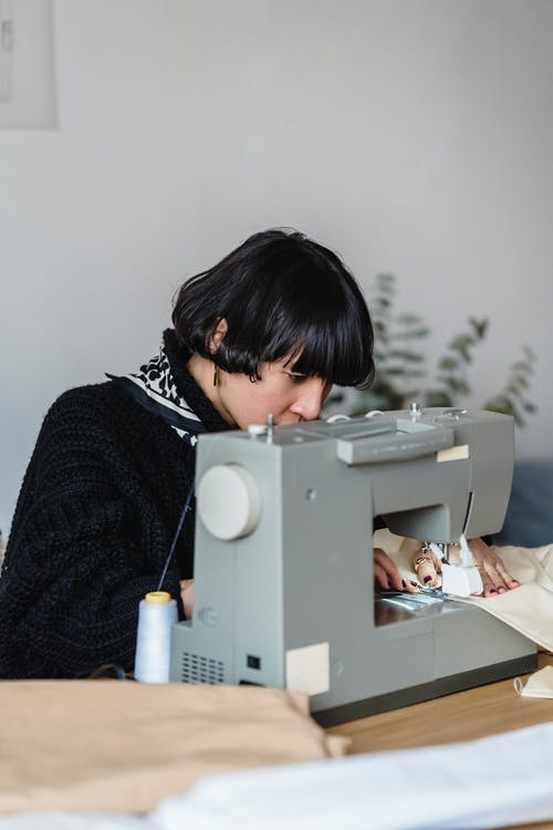 Side view of concentrated Asian female tailor using sewing machine while working at table with fabric in modern light studio