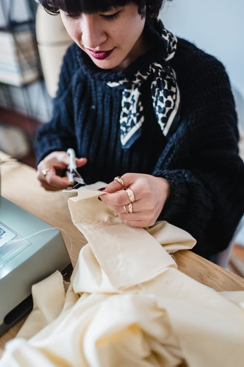 From above of crop Asian female dressmaker with black hair cutting textile with scissors while working at table in light atelier