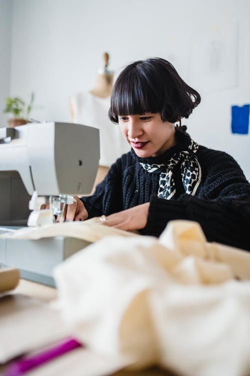 Concentrated Asian woman sewing fabric