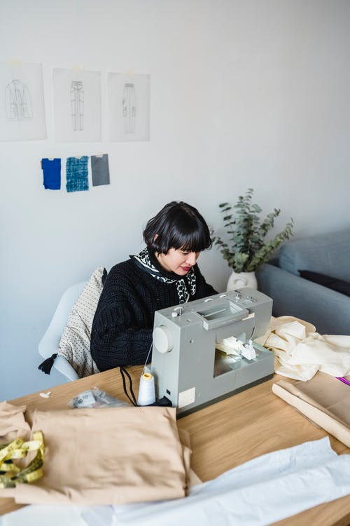 Young Asian seamstress sewing on machine in workshop