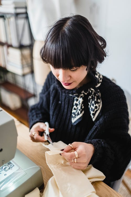 Focused trendy young ethnic female sewer with dark hair cutting piece of fabric with scissors while creating new dress in workshop