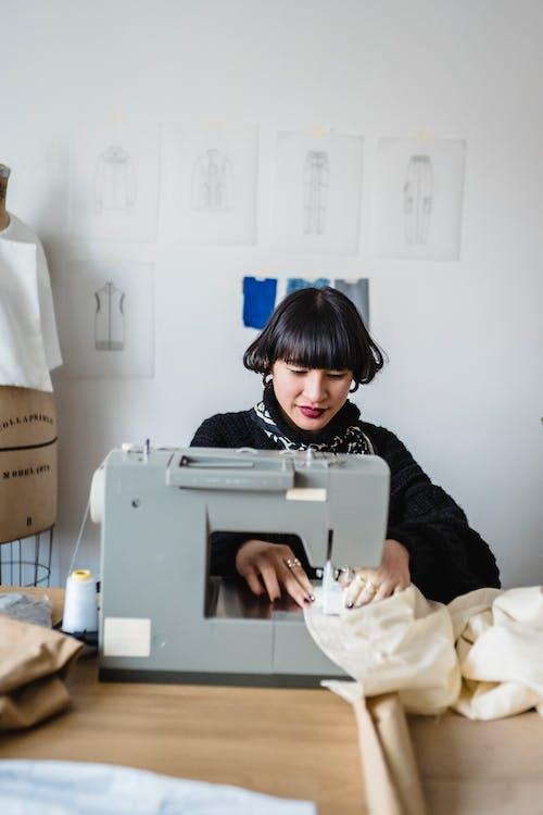 Stylish ethnic female dressmaker sewing dress with machine in workshop