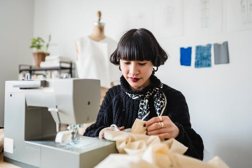 Fashionable young Asian seamstress with dark hair and red lips in stylish knitted sweater cutting fabric with scissors while sewing dress with machine in light modern