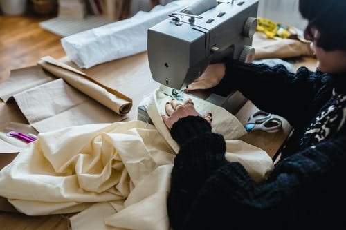 From above of crop female sewer in stylish warm sweater stitching fabric with sewing machine while working in traditional atelier