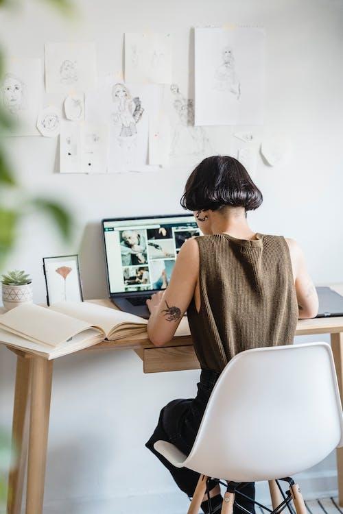 Anonymous female freelancer using netbook in light workshop