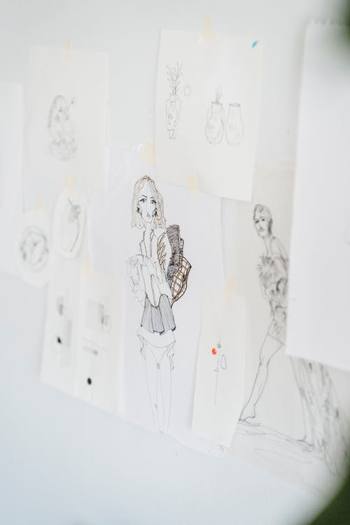 Paper with different many black sketches hanging on wall on white background in daylight