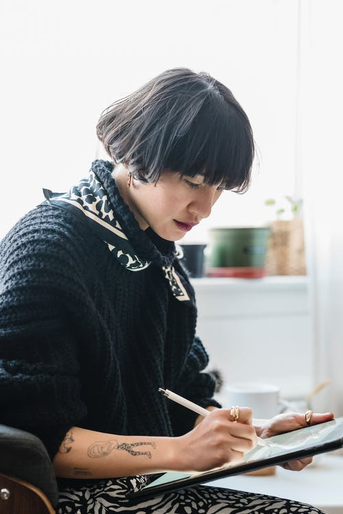 Side view of crop ethnic female with short hair and tattoos on hands working with stylus and graphic tablet