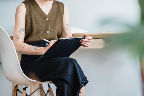 Crop woman drawing in tablet while sitting on white chair