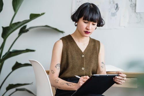 Young ethnic female artist drawing in graphics tablet with stylus while sitting on white chair near plant in light room
