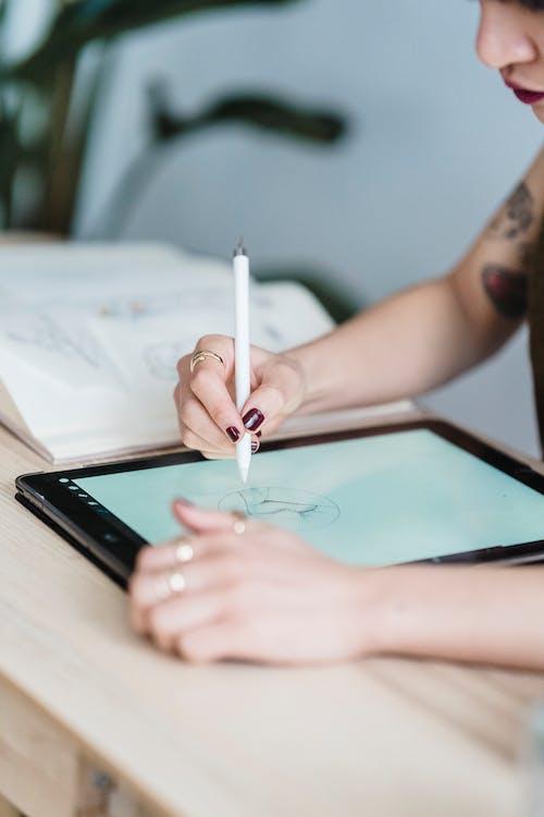 Crop female artist drawing sketch in tablet