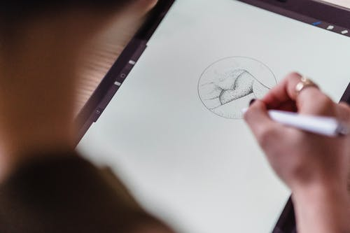 From above of crop anonymous artist with stylus in hand drawing creative sketch on graphics tablet