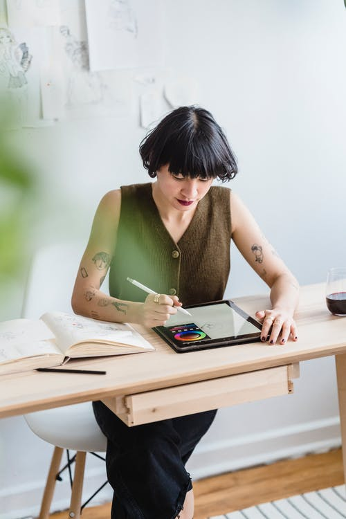 Asian woman drawing on graphics tablet while sitting in studio