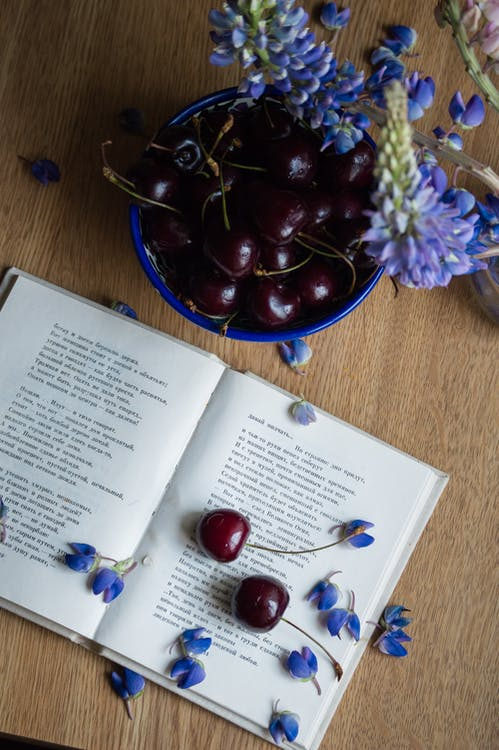 Top view composition of opened compelling book arranged on wooden table with ripe cherries and tender blue flower petals