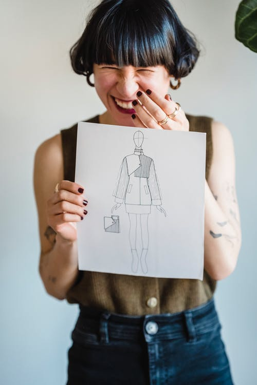 Crop happy young Asian female designer demonstrating paper sheet with fashion illustration and laughing against white background