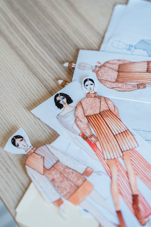 Collection of drawn fashion sketches on wooden table