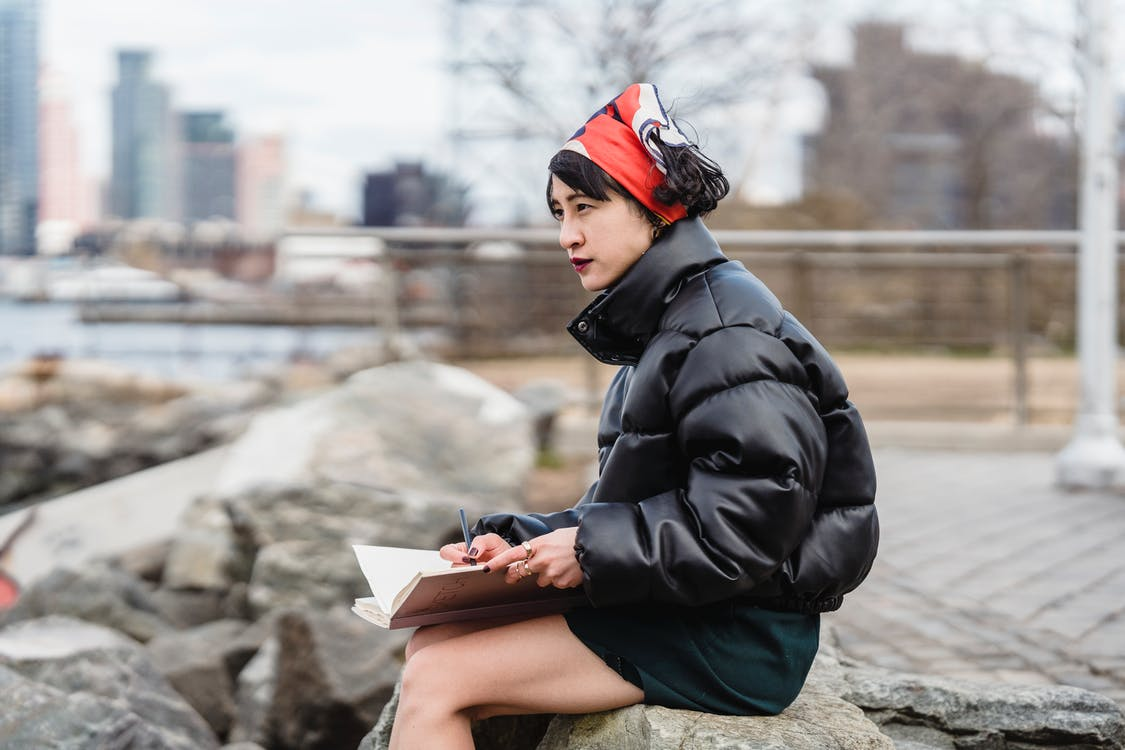 Young ethnic female artist admiring river and city and drawing in sketchbook