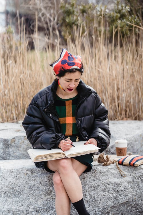 Thoughtful Asian female artist in stylish clothes sitting with leg crossed on stone and drawing in sketchbook in nature in daylight