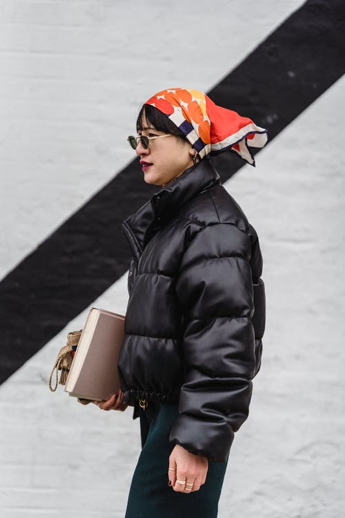 Side view of female in stylish round shaped sunglasses and black warm jacket looking away near white wall with black stripe