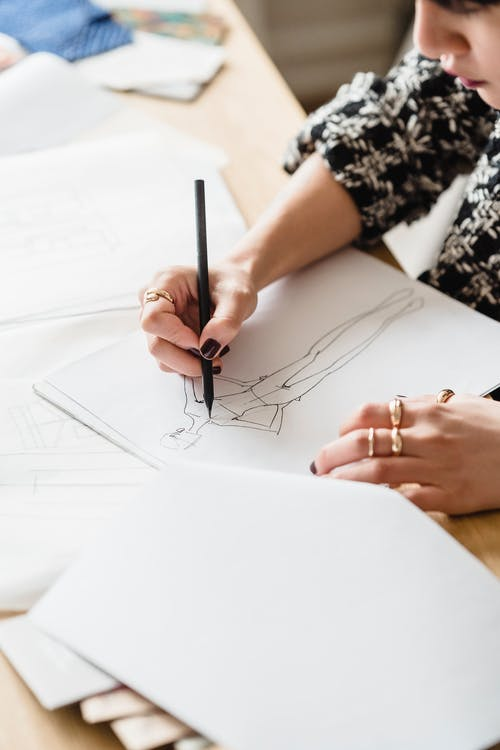 From above of crop anonymous female designer sitting at table and drawing sketches in light workspace in daytime