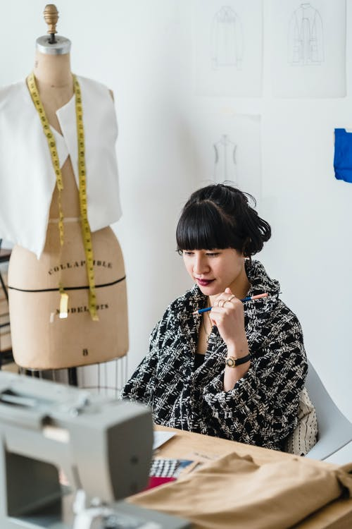 Young Asian seamstress working in light atelier in daytime