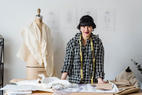 Positive Asian female dressmaker with measuring tape on neck standing at wooden table with fabrics during work in atelier in daytime