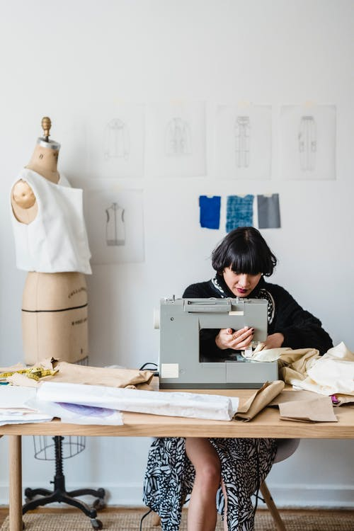 Concentrated Asian female dressmaker sitting at table and sewing on sewing machine against wooden mannequin in light atelier