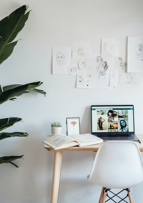 Laptop and opened book placed on wooden table near light wall with paintings in apartment in daytime