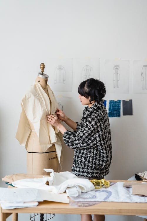 Woman sewing measuring fabric on mannequin in atelier