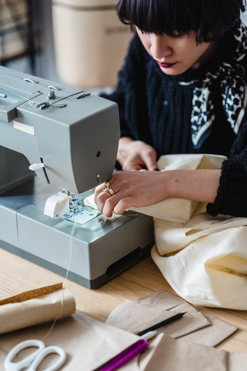 Crop concentrated female designer in casual clothes sewing new collection in light atelier in daytime