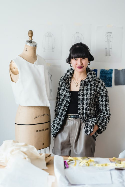 Cheerful young Asian woman designer in stylish clothes standing near mannequin against wall with sketches and looking at camera in atelier