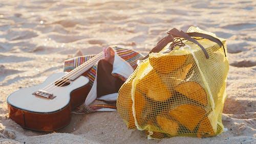 Guitar and Bag of Firewood on Beach Sand