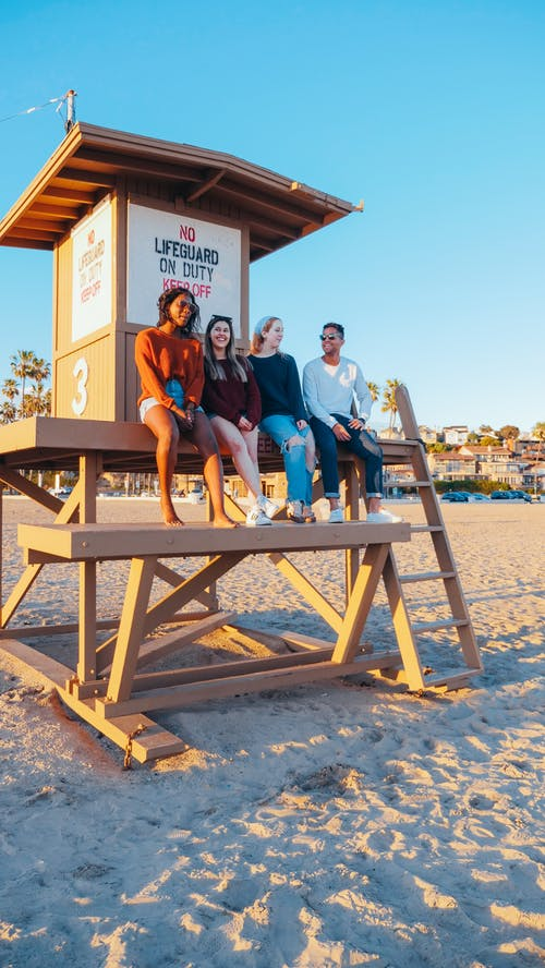 Group of Friends Sitting on Lifeguard Tower