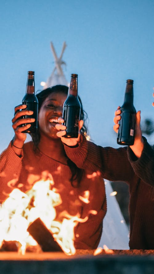 Woman with Her Friends Holding Beer Bottles