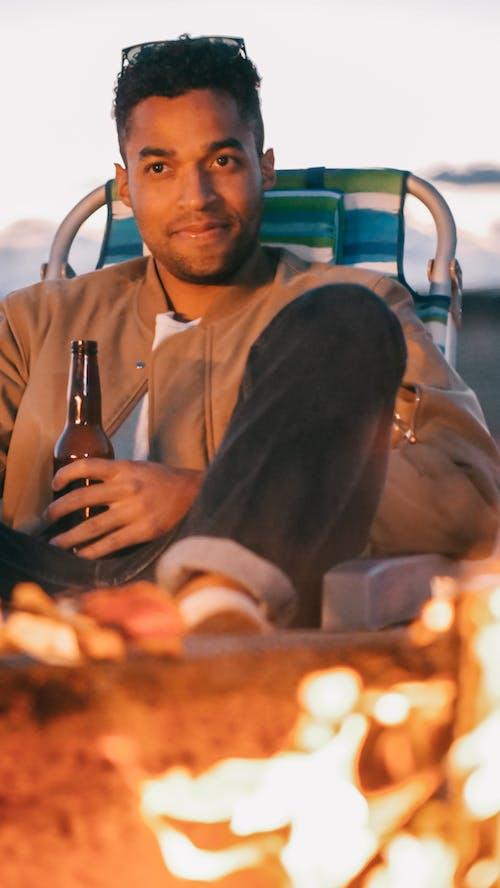 Man Holding Beer Bottle in front of a Bonfire