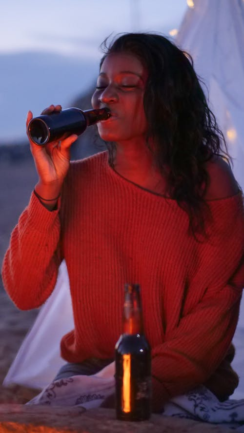 Woman in Pink Knit Sweater Drinking Beer