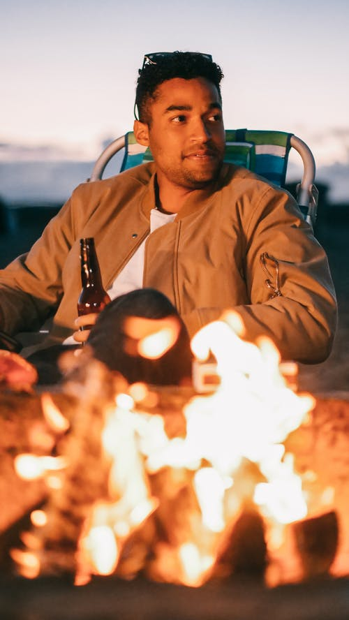 Man Sitting Holding a Beer Bottle