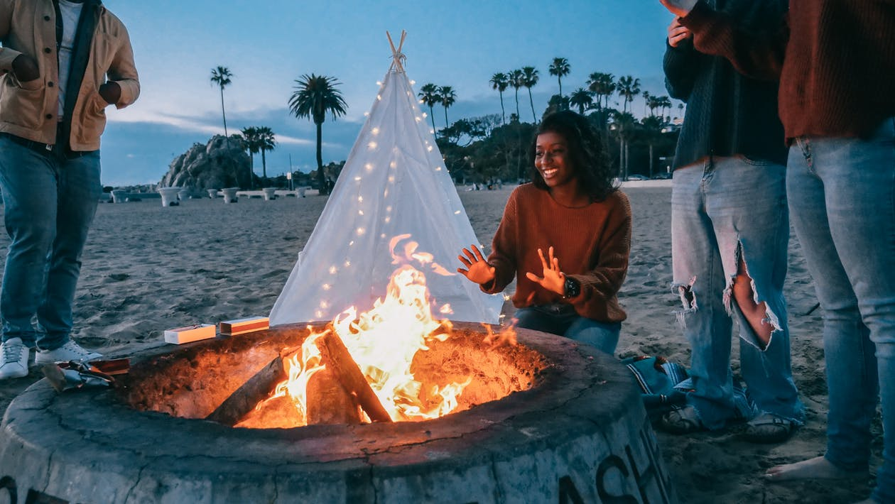 Woman Warming Her Hands in Front of the Fire Pit