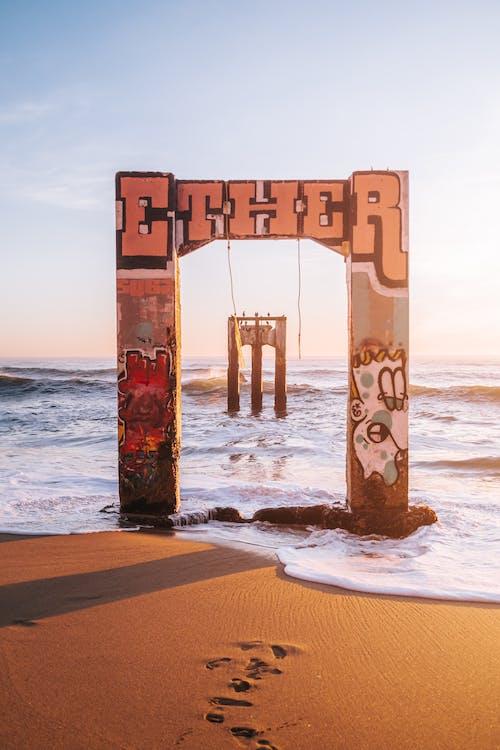Brown Wooden Cross on Beach Shore